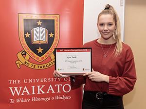 Nyssa Hewitt holding her diploma